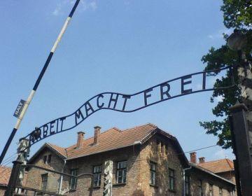 De spreuk Arbeit macht frei op de toegangspoort van Auschwitz I - CC