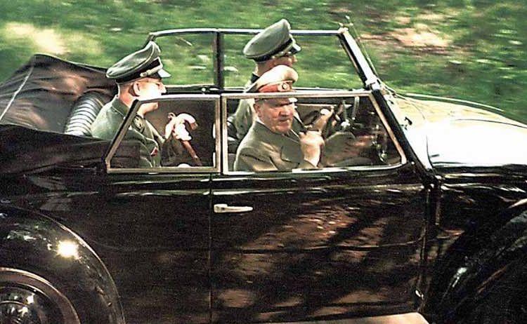 Adolf Hitler wordt na de eerste steenlegging van de Volkswagen-fabriek in 1938 door zijn vaste chauffeur Erich Kempka rondgereden in een Kever cabriolet met achterin Heinrich Himmler.