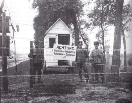 Grenswachten achter de 'draden des doods'; een electrische grensversperring van 2000 volt van 450 km lang tussen Nederland en België, door Duitse troepen aangelegd, om smokkel en illegale grensoverschrijding tegen te gaan. Daardoor warten er minder Duiitse grenssoldaten nodig.