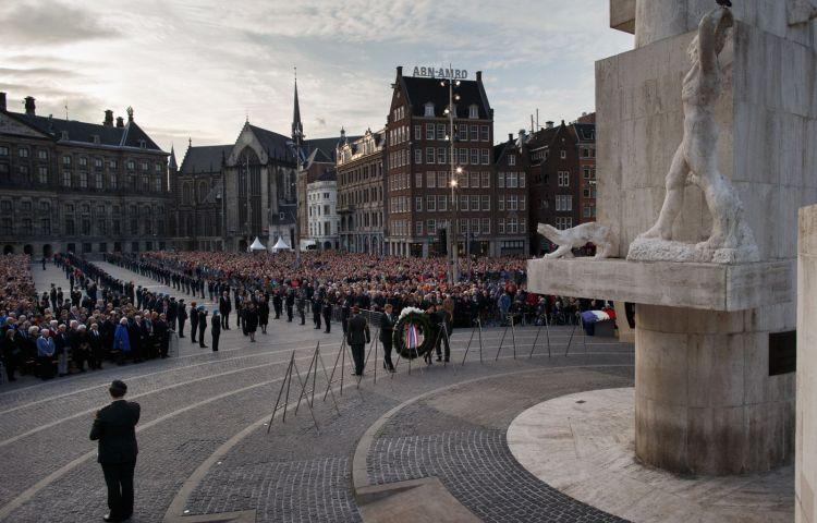 De Koning en Koningin leggen de eerste krans vlak voor de twee minuten stilte bij het Nationaal Monument op de Dam in Amsterdam.