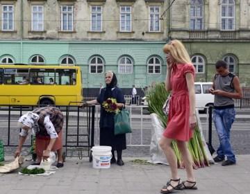 Een paradox tussen oud en jong - oudere vrouwen verkopen zelfgekweekte groente op straat. Jongeren zijn druk met hun mobieltje. (Lviv, stad van paradoxen)
