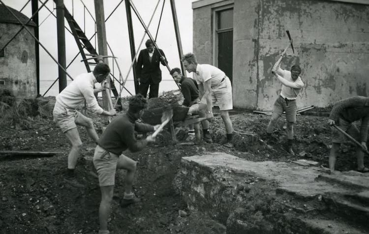De studenten van Arie de Froe (met pak) aan het werk op Schokland. Collectie Nieuw Land Erfgoedcentrum, Lelystad.