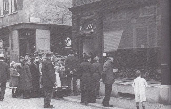 In Haarlem staat een rij mensen voor een slagerij om eenheidsworst te halen, anno 1918.