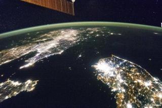 Vanuit een satelliet lijkt de laatste Noord-Koreaan 's nachts het licht uit te hebben gedaan. Het land vertoont zich op de aardbol als een 'zwart gat'. (Foto 2015, NASA, Tech Insider)