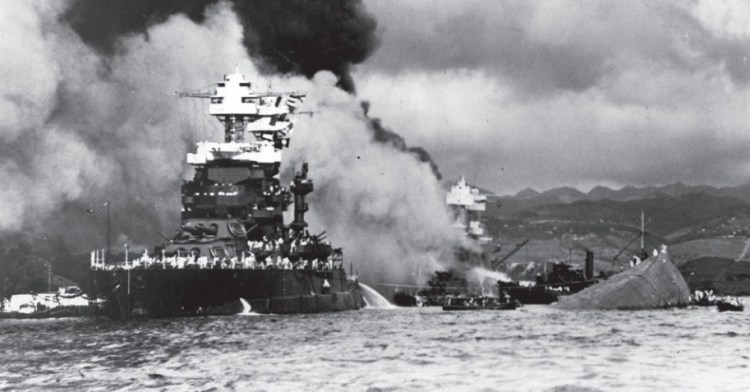 De aanval op Pearl Harbor, 7 december 1941. De uss Maryland naast de gekapseisde uss Oklahoma; de uss West Virginia staat in brand.  © Naval Historical Foundation, Washington DC