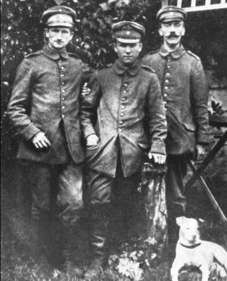 Deze in april 1915 in Fournès genomen foto is voor zover bekend de eerste foto van de regimentskoeriers Ernst Schmidt, Anton Bachmann en Adolf Hitler. Aan Hitlers voeten de foxterriër Foxl, die op een dag aan is komen lopen en sindsdien Hitlers favoriete metgezel is.