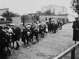 Kinderen in het getto van Łódź op weg naar de treinen die hen naar de vernietigingskampen brengen (USHMM)