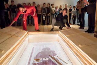 Janneke Berkelbach (links) van de Nationale Archeologiedagen en gedeputeerde Henri Swinkels openen het eerste graf en onthullen daarmee de Merovingische schat in het Museum voor Religieuze Kunst in Uden