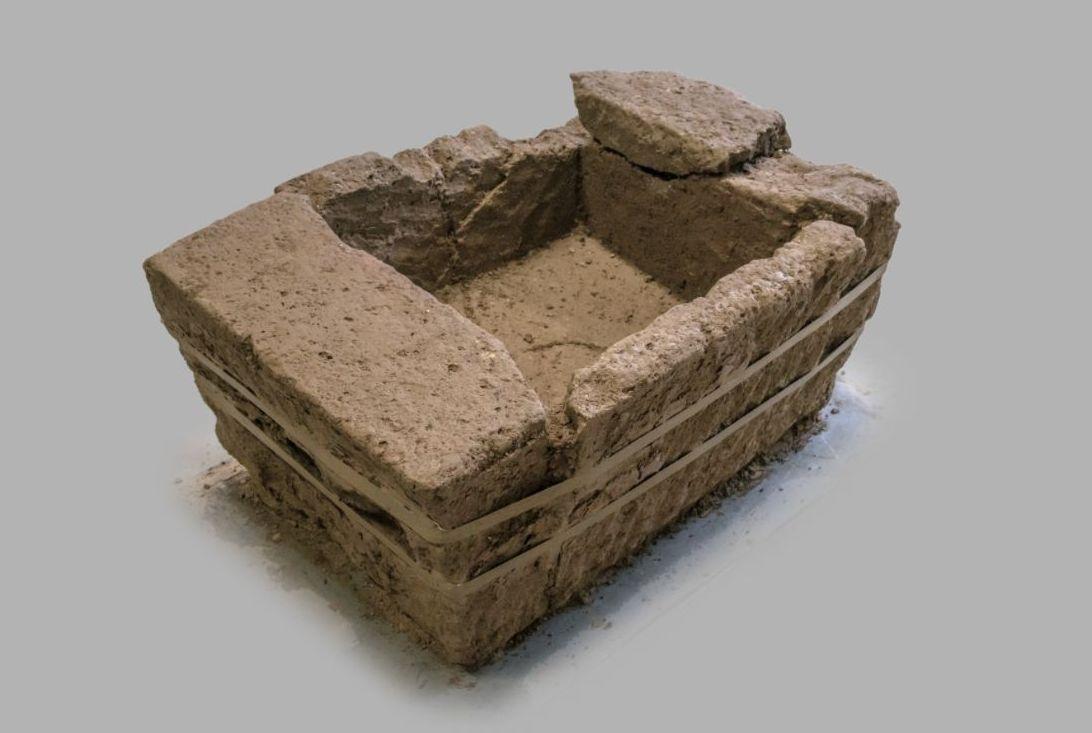 Vier askisten uit tufsteen, gehouwen uit bouwelementen. In de vier redelijk intacte kisten zijn de crematieresten bijgezet. De kisten zijn afgesloten geweest met dakpannen, vloertegels of mogelijk houten planken. (RWS)
