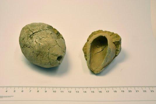 Twee van de dertien eivormige smeltkroesjes. De linker is compleet, de rechter is gebroken waardoor de holte aan de binnenkant goed zichtbaar is. (RCE)