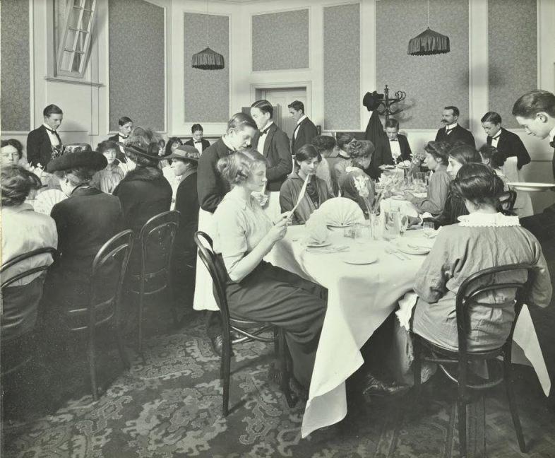 Leerling-koks en -obers serveren een maaltijd in één van de restaurants van de Hotel and Restaurant School. Foto Collectie London Metropolitan Archives.