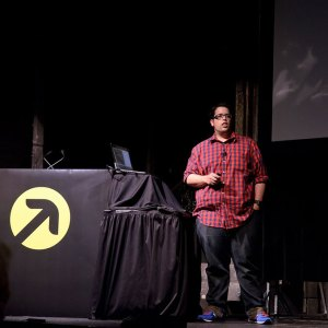 Jesse Friedman on stage speaking at a conference