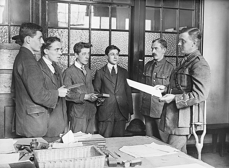 As an army officer reads out the oath, four young men hold Bibles and confirm their allegiance at a recruitment office. Probably taken in 1917, Imperial War Museum, Q 30071