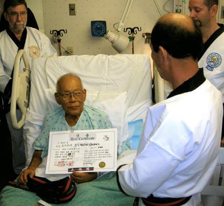 Walter Okahara receiving 4th Dan rank certificate from Kwan Jang Nim H.C. Hwang