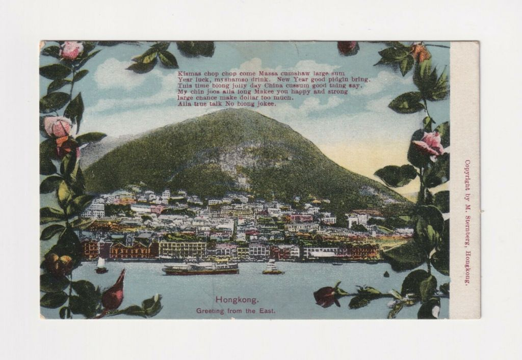 A postcard from Hong Kong, dated 1910. It shows Hong Kong as a small port city, with a mountain in the background. In the top centre, there is a Christmas greeting in Pidgin English.
