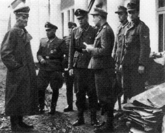 This grainy photograph is one of the few surviving images of Dirlewanger, seen here on the left in a long trench coat, with his staff