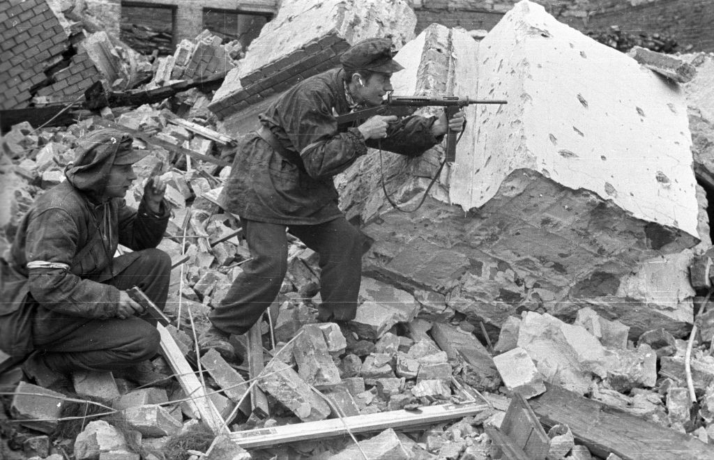 Polish resistance fighters, recognisable by their armbands, stalk through Warsaw's ruins during the Uprising