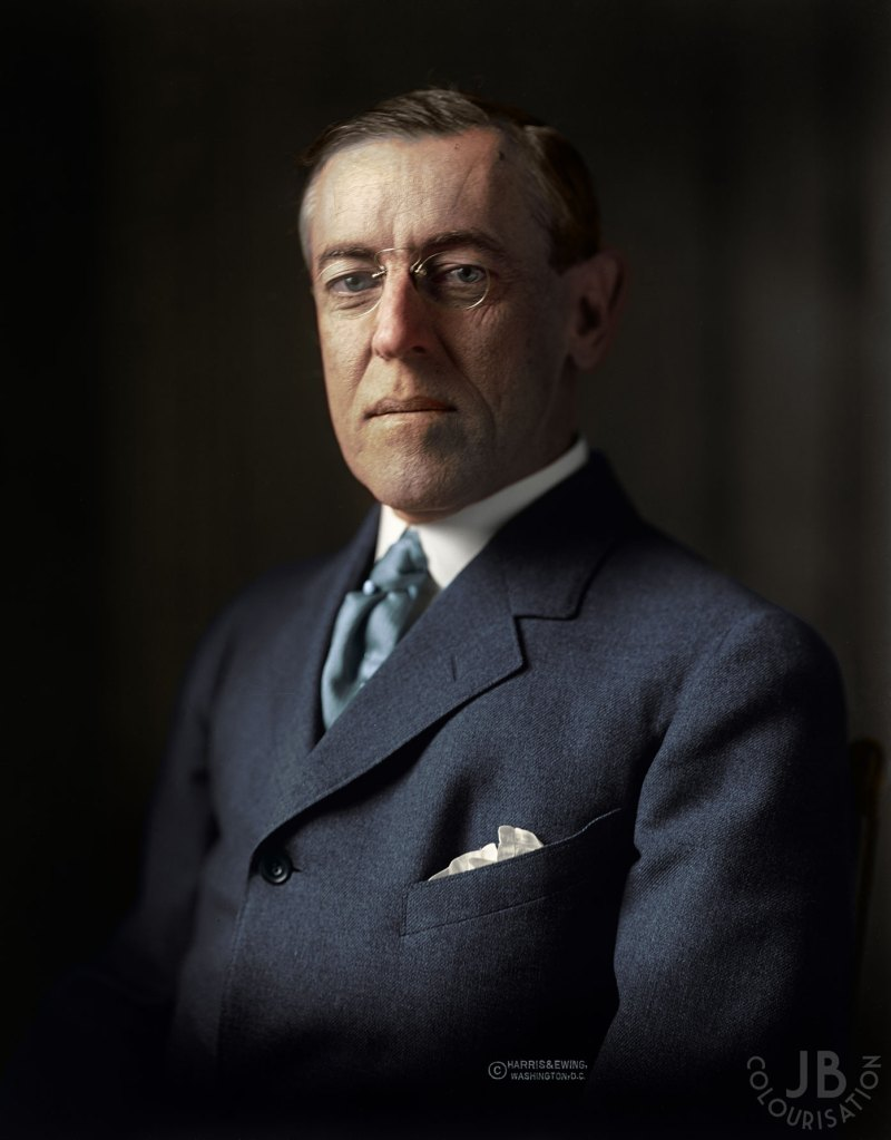 Woodrow Wilson wearing a suit and glasses. Colorized photograph.