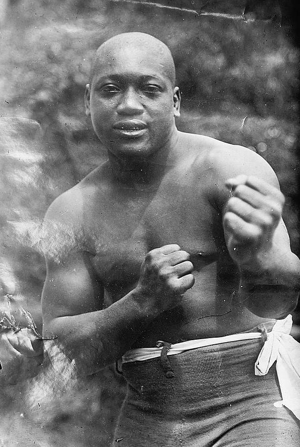 Legendary boxing heavyweight champion Jack Johnson with his fists up posing for a photograph.
