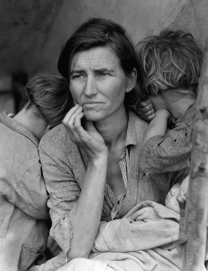 The Migrant Mother, Florence Owen Thompson photographed with her hand on her face with a concerned look. She is surrounded by her children looking distressed. Taken in March 1936 during the Great Depression by Dorothea Lange for the Farm Security Administration