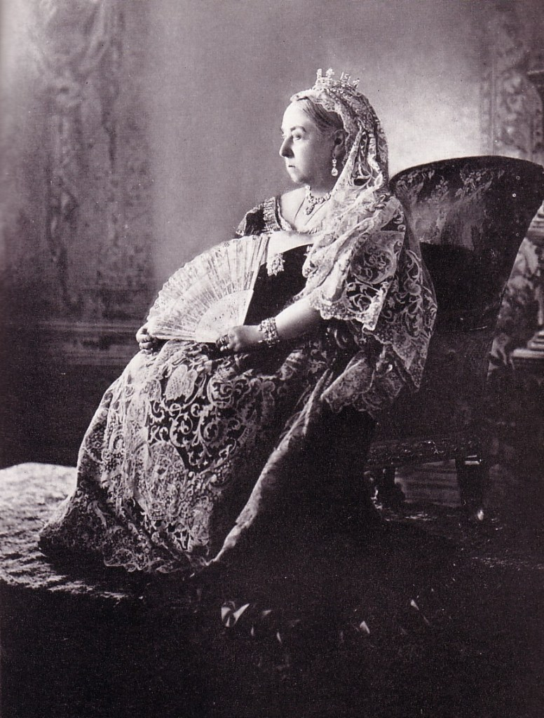 Queen Victoria sitting on a chair with a fan in her hand.