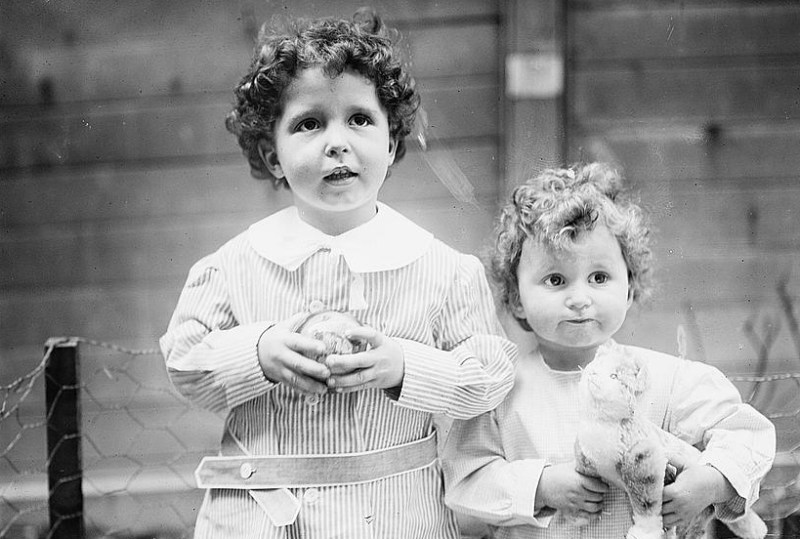 Brothers holding toys being photographed shortly after returning to land after surviving the titanic. Both are not aware the significance of what just happened.There is a chain fence and wooden wall behind them.