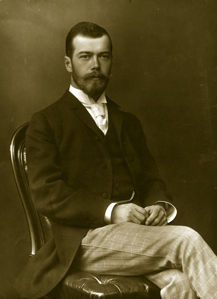 An uncropped version of the previous photo, shows Nicholas II of Russia in a suit sitting on a chair and posing for a photograph at the wedding of George and Mary of the United Kingdom in 1893.