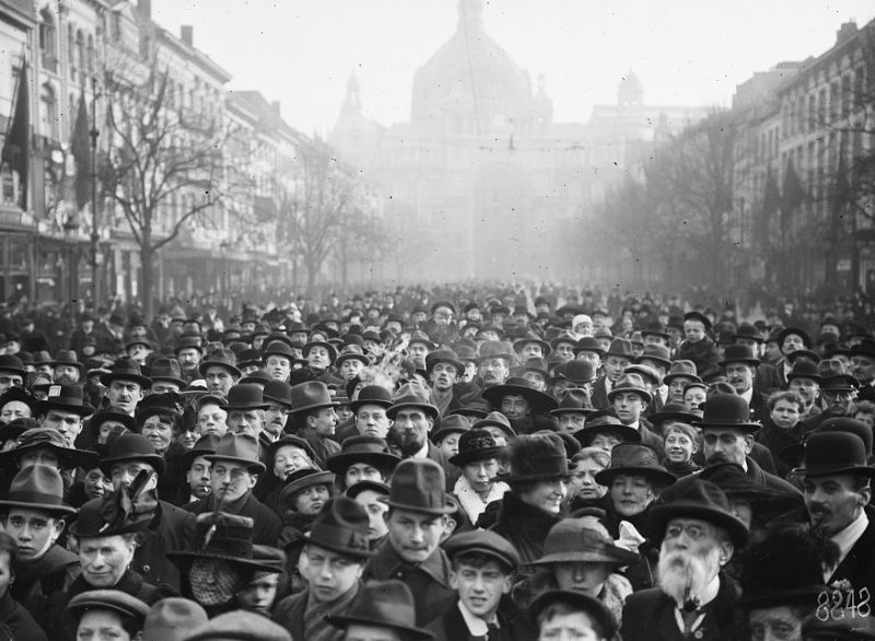 Photograph of thousands of people crowd the street in Antwerp to celebrate armistice in 1918