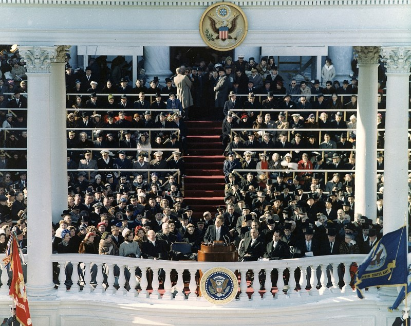 John F Kennedy, President of the United States, saying his inaugural address during his inauguration at Washington, DC on January 20th 1961. He is surrounded by man others.