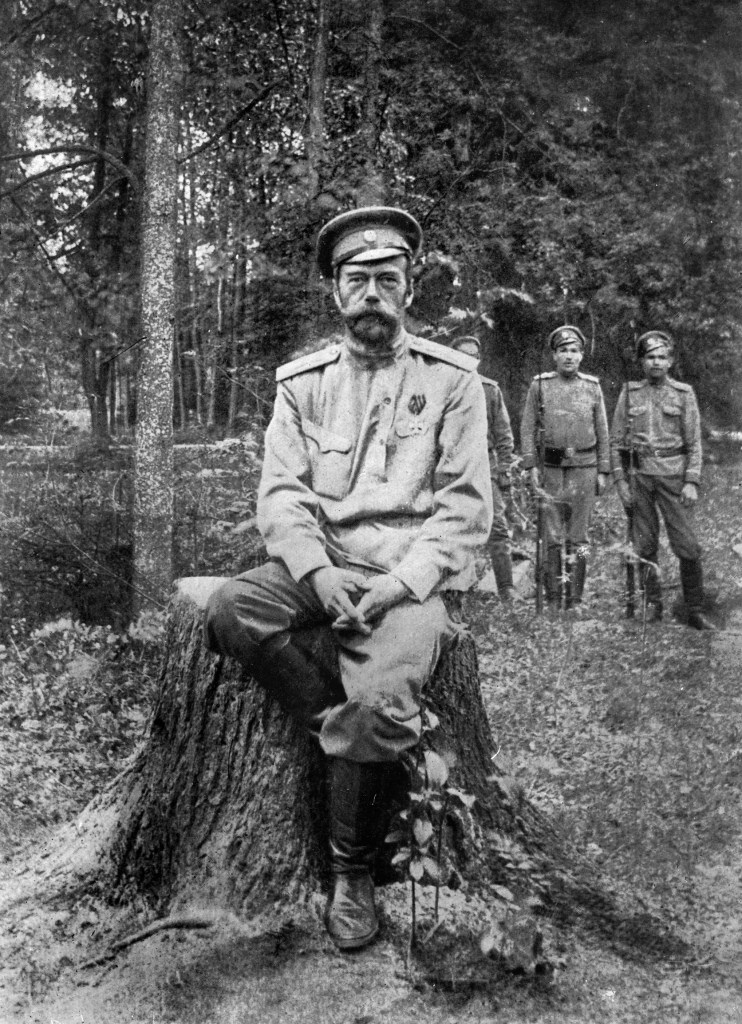 Nicholas II photographed sitting on a tree stump with guards behind him in 1917 it is believed to be his last photo.