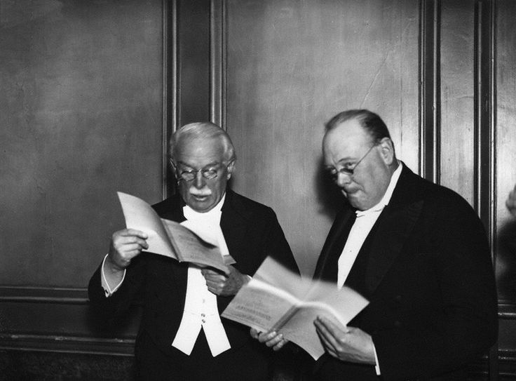 David Lloyd George wearing glasses and reading a book, standing next to Winston Churchill also wearing glasses and reading a book. Both are in formal wear. Taken in 1934.