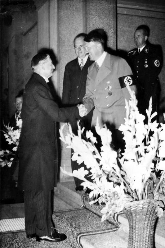 British Prime Minister Neville Chamberlain shaking hands with Adolf Hitler outside a hotel in Bad Godesberg. Paul Schmidt and Otto Dietrich stands behind Hitler. Taken on September 24th 1938.