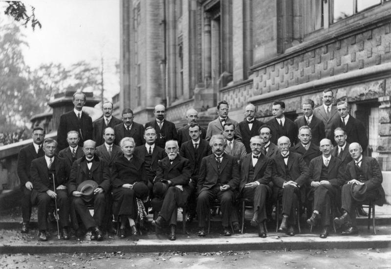 Key attendees of the 1927 Solvay conference photographed sitting down and in suits. The names are Auguste Piccard, Émile Henriot, Paul Ehrenfest, Édouard Herzen, Théophile de Donder, Erwin Schrödinger, Jules-Émile Verschaffelt, Wolfgang Pauli, Werner Heisenberg, Ralph Howard Fowler, Léon Brillouin, Peter Debye, Martin Knudsen, William Lawrence Bragg, Hendrik Anthony Kramers, Paul Dirac, Arthur Compton, Louis de Broglie, Max Born, Niels Bohr, Irving Langmuir, Max Planck, Marie Skłodowska Curie, Hendrik Lorentz, Albert Einstein, Paul Langevin, Charles Eugène Guye, Charles Thomson Rees Wilson, Owen Willans Richardson