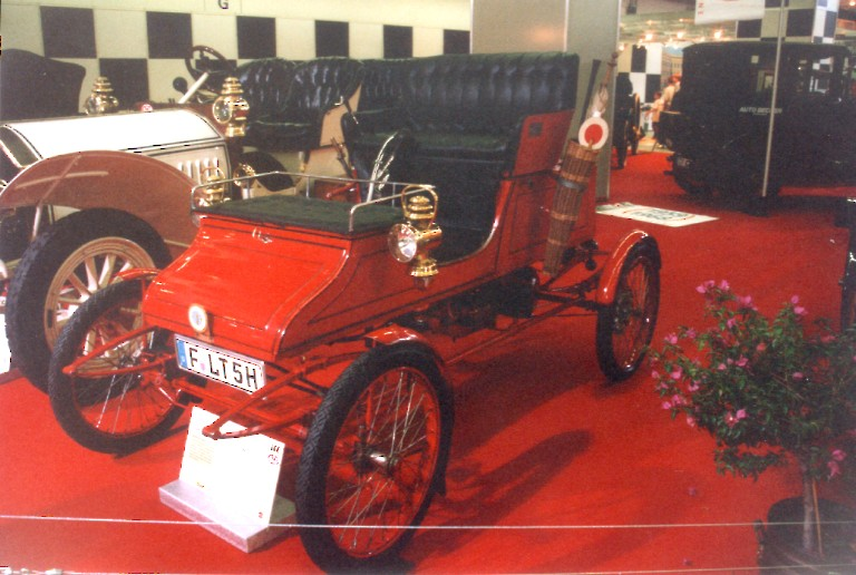 A red Stanley Steamer steam car from 1900 - 1906 on display at a museum.