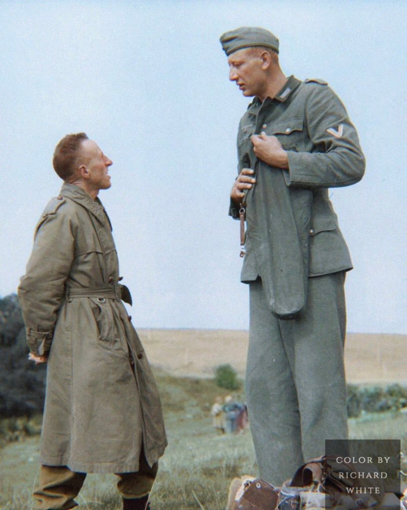 The tallest soldier to fight in World War 2, Jakob Nacken wearing his military uniform talking with a Canadian soldier wearing a trench coat in September 1944. The photograph is colorized