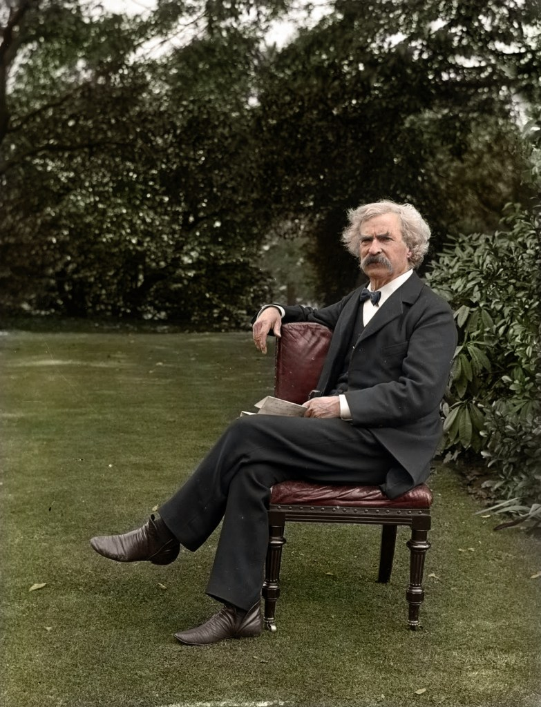 Colorized photo of Mark Twain sitting on a chair in his garden in circa 1900.