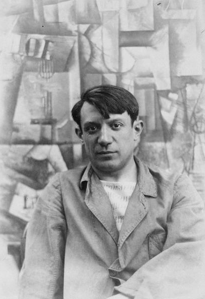 Picasso photographed in front of one of his paintings.