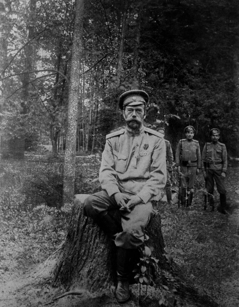 Last known photo of Nicholas II. He is sat on a tree stump with soldiers behind him.