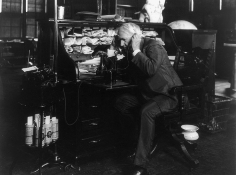 Thomas Edison using a telephone