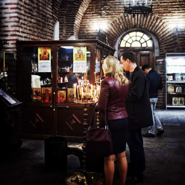 A couple lighting prayer candles in the church of St. Sofia