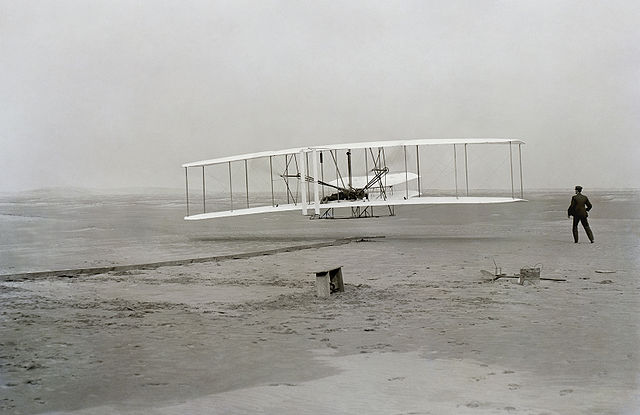 The only photograph of the Wrights' airplane in flight on the historic day. Orville is piloting, and Wilbur is on the right.