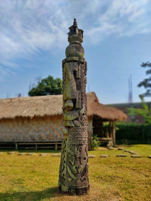 A sculpted Totem pole with intricate carvings is planted at the centre of the complex