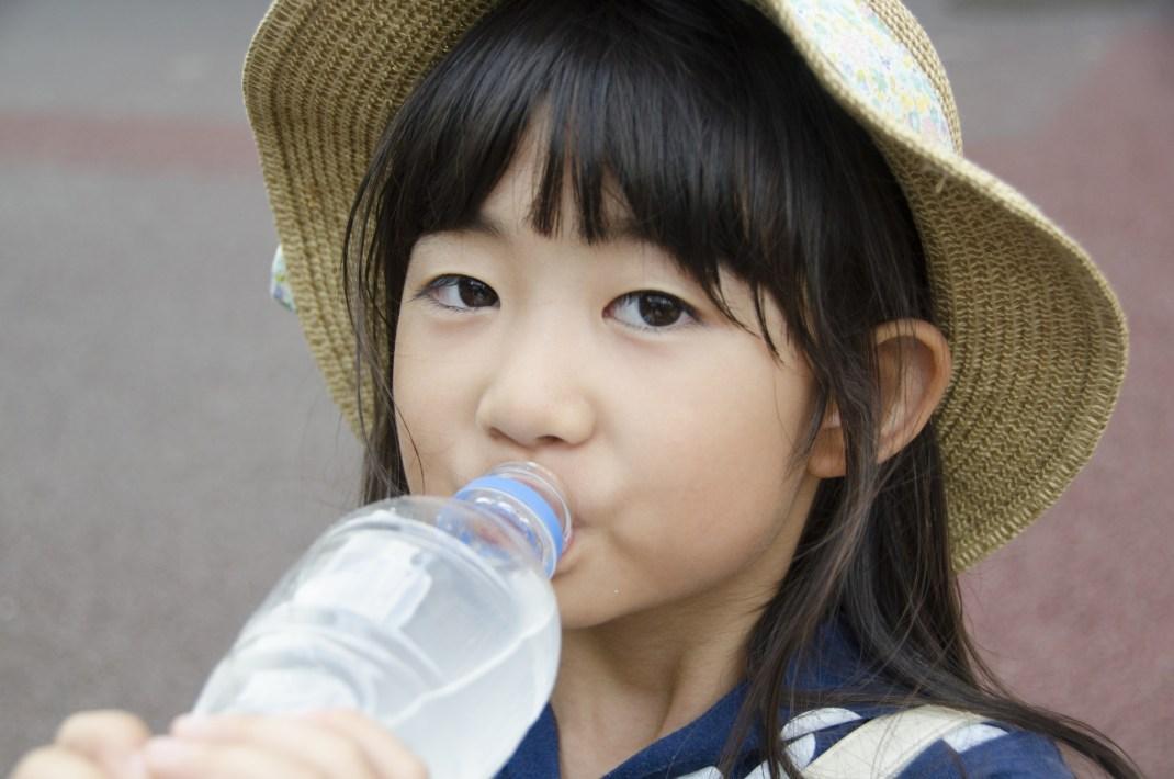 帽子をかぶって水を飲む女の子