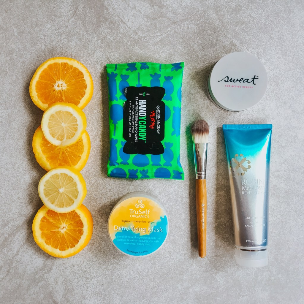 Summer skincare beauty essentials flatlay featuring Robin McGrow Revelation, Sweat Cosmetics, and TruSelf Organics