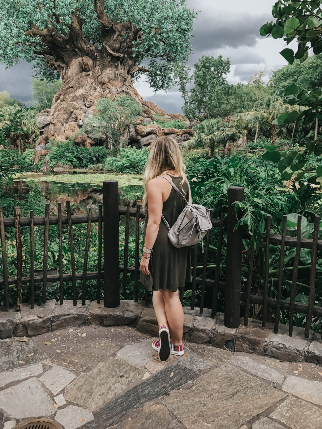 At Animal Kingdom's Tree of Life wearing an olive shift dress, ISKAY colorful handmade shoes, @kutukakiss bracelets, and @violetrayny backpack.
