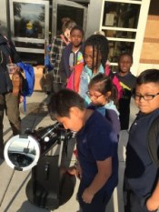 Families at Richard M. Daley Library in Chicago look through a reflector telescope to safely view the Sun. A special cap on the front of the telescope blocks most of the Sun's light, making the Sun safe to see.