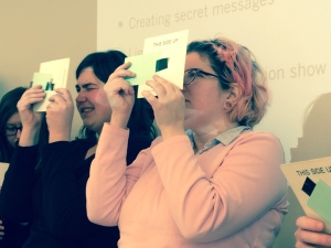 Two Chicago Public Library staff members hold diffraction grating sheets in front of their eyes to see the different colors in white light.