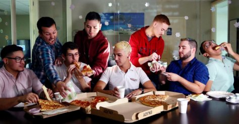 image of men sitting around a table and eating Pizza