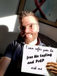 man holding sign saying I can refer you to free HIV testing