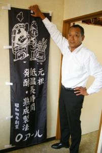 代表の河合和彦さん。取材日に新しくできたばかりののぼり旗と(箕輪町の本店事務所にて撮影)